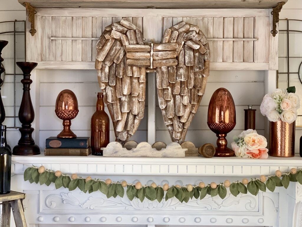 felt leaf garland with speckled eggs displayed on a white mantel with farmhouse decor