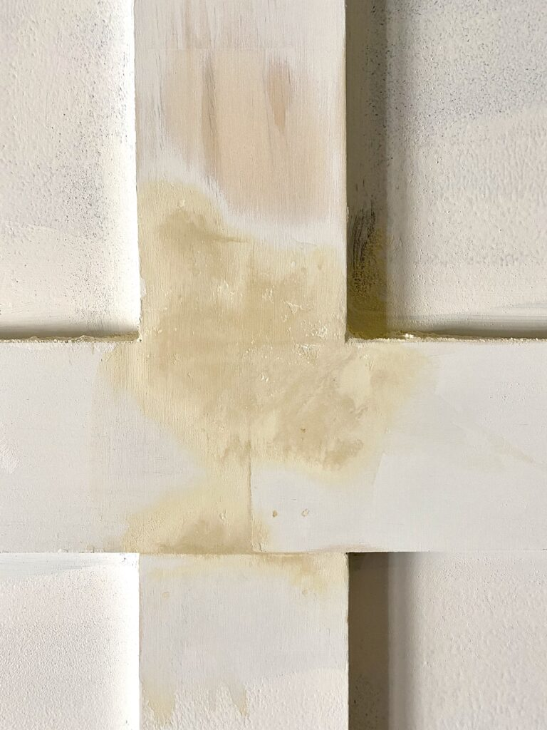 sanding wood filler in the seems of a DIY board and batten bedroom wall