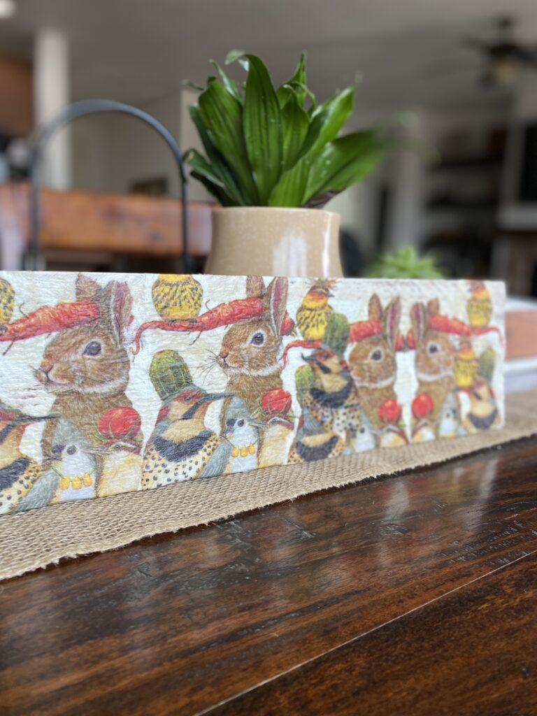 A decoupage sign with bunnies and other animals.