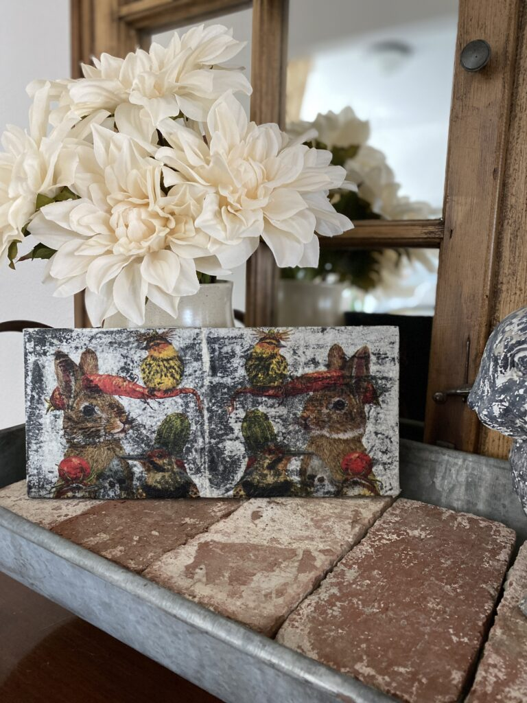Flowers with a DIY decoupage sign project on brick