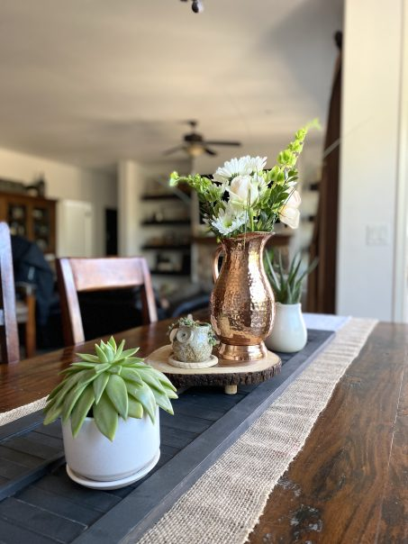 Simple Spring Dining room table decor idea with a black shutter and copper pitcher
