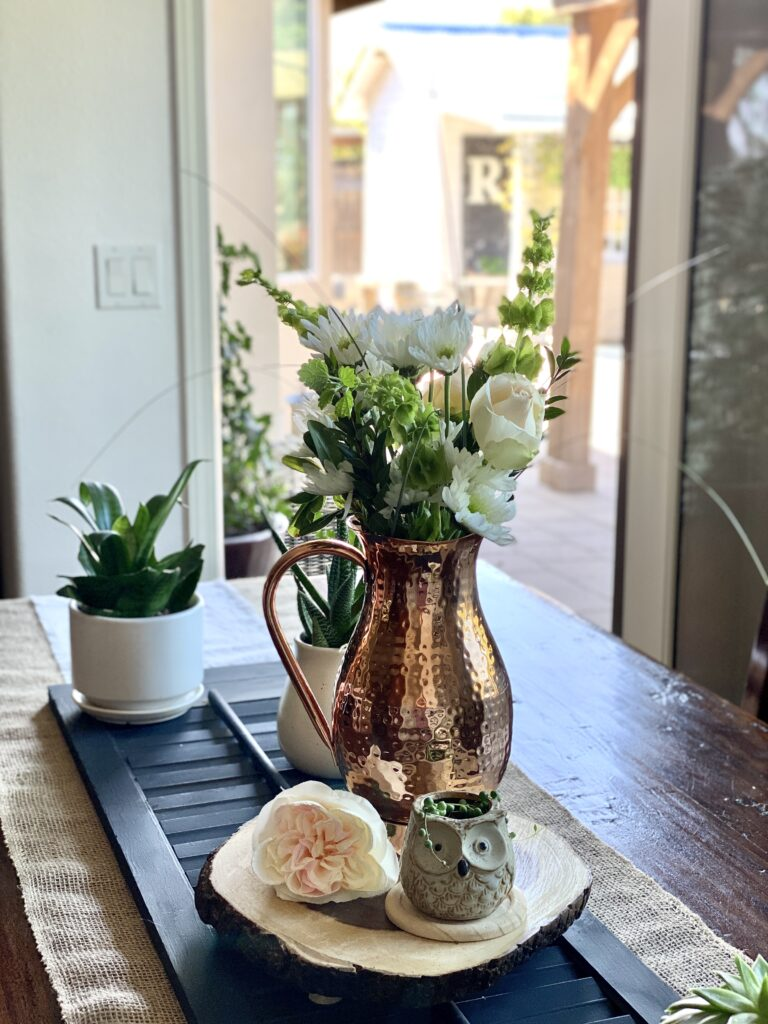 A dining table with a simple spring tablescape using a copper pitcher, white pots and succulents.